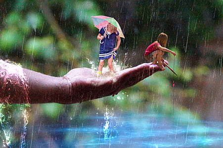 two children's enjoying the rain during daytime