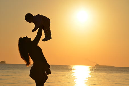 silhouette of woman carrying baby