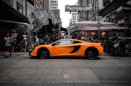 orange supercar along street at daytime