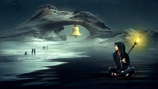 woman holding light post sitting on beach sand