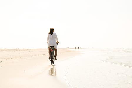 photo of woman riding bicycle near seashore