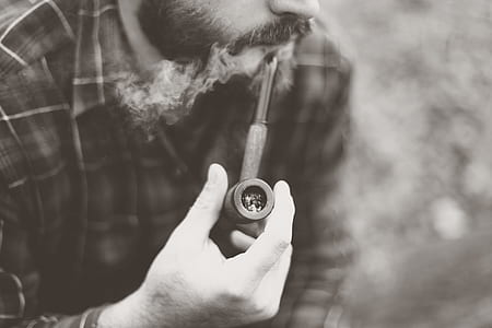 Grayscale Photo of Man Holding Tobacco Pipe
