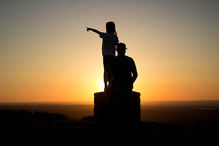 silhouette photo of man and girl during golden hour