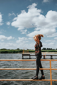 Beautiful blonde woman on a wooden pier by the lake