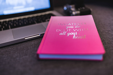 Pink notebook with a silver laptop and a camera