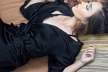 woman wearing black satin robe lying on brown surface