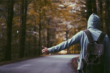 person standing wearing backpack between trees