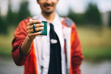 person holding green mug