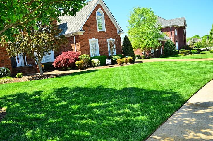 brown brick house near green grass field