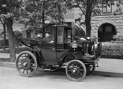 grayscale photograph of three men and one woman riding classic black vehicle