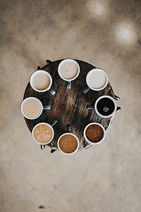 eight cups with coffee on brown wooden table