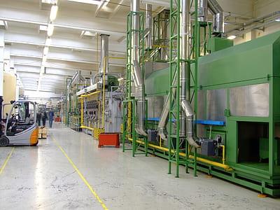 gray forklift near green industrial machine