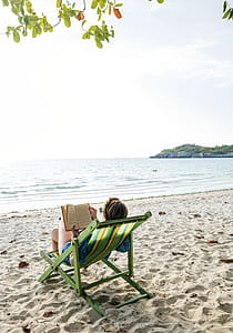 photo of woman reading book near seashore
