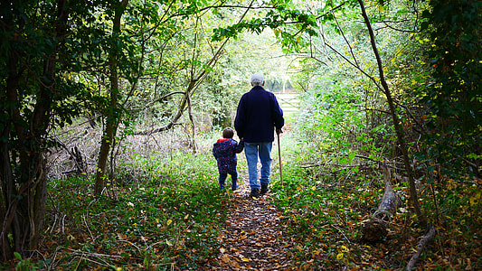 man and boy holding hands walking dirty pathway towards forest