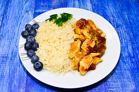 chicken dish and blueberries on white ceramic plage