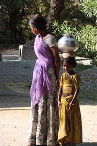 woman standing beside girl wearing sari dresses