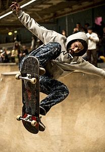 man in gray hoodie riding skateboard
