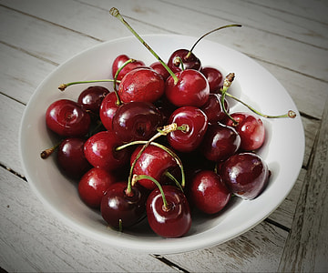red cherries on white bowl