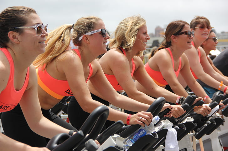 five women in pink sports bra on stationary bike