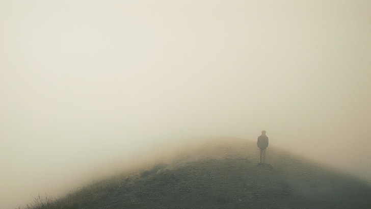 man standing on high-ground surrounded by mist during daytime