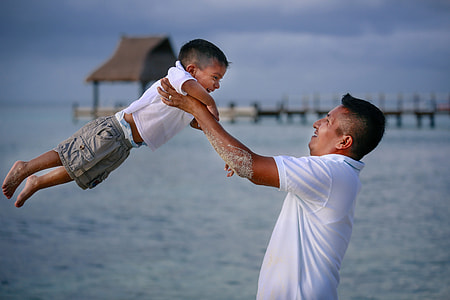 man carrying a boy in white polo shirt selective focus photography