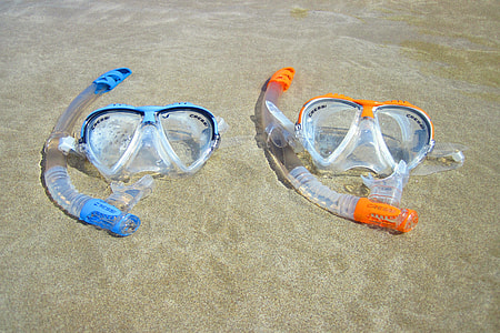 two snorkel and goggles on beach shore