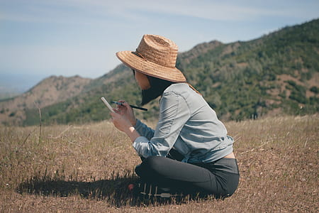 woman holding makeup brush sitting on grass field