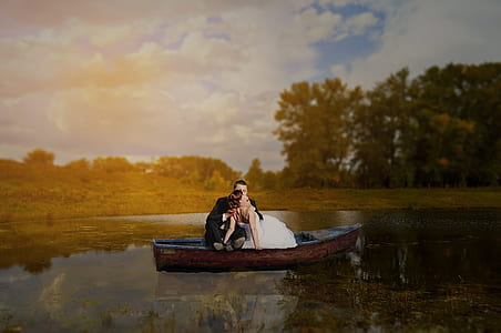 man and woman on brown wooden boat