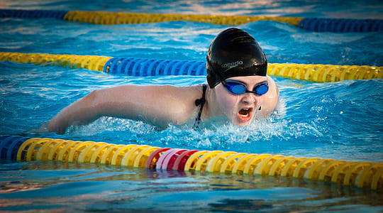 person wearing black swim cap and blue goggles