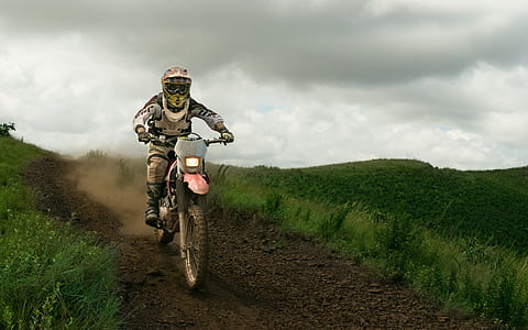 man riding dirt bike full in gear during daytime