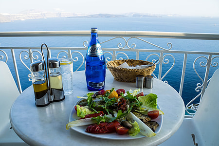 photo of table with vegetable salad near blue bottle, basket, and cruets