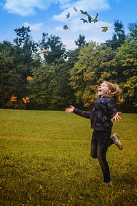 Girl in Black Jacket Standing on Green Grass during Daytime