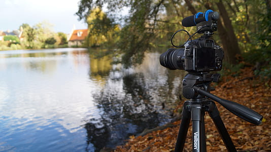 black DSLR camera with tripod stand near body of water