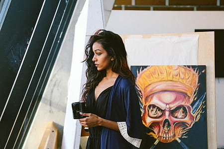 woman in front of skull painting in blue robe