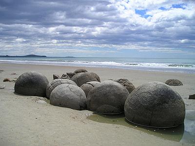 black rocks beside ocean during daytime