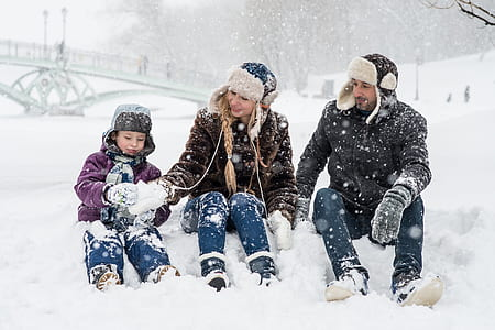 man, woman, and boy sitting on snow ground making snowballs