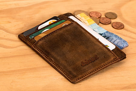 brown leather wallet with banknotes and coin