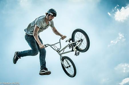 man ramping gray BMX bike