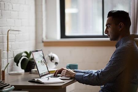 man wearing dress shirt in front of laptop computer
