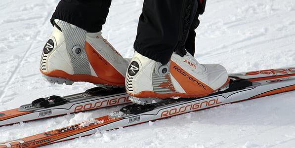 person on white and orange Rossignol snow skis photo