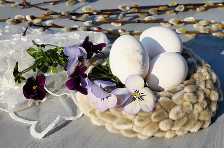 purple petal flower with eggs on fabric nest