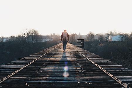 man walking through train rail