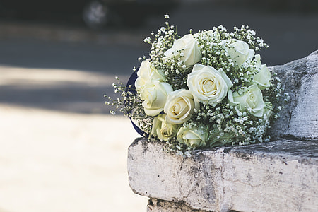 white rose bouquet on white concrete fence