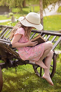 girl wearing pink and multicolored floral cap-sleeved dress while sitting on brown wooden carriage