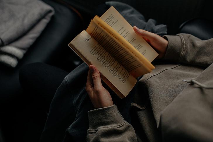 man wearing gray sweatshirt reading book