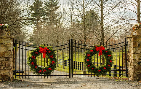 two large Christmas wreaths hanging on metal double gate