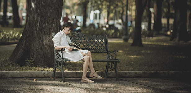 Woman Sitting on Metal Bench on Park While Reading Book