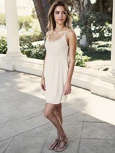 blonde hair woman in white spaghetti strap dress