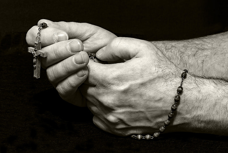 grayscale photo of human hands holding rosary
