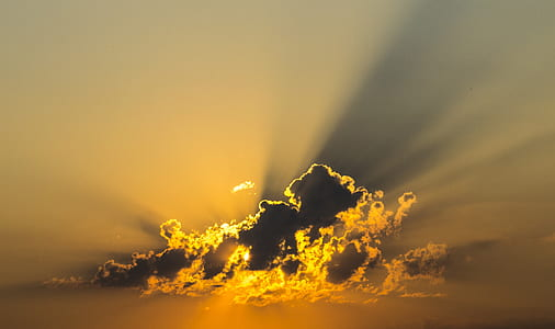 sun covered by clouds emitting sun ray